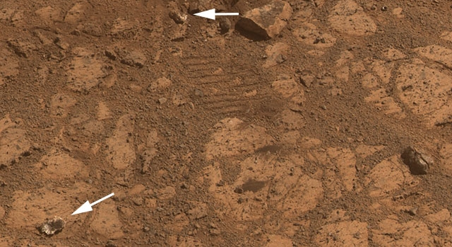 "The reality: from its revised position, Opportunity reveals ""Pinnacle Rock"" (arrowed lower left) to have been broken-off of a small rock (top centre) by the rover's passage (note the wheel tread marks top centre), and temporarily lodged in the wheel"