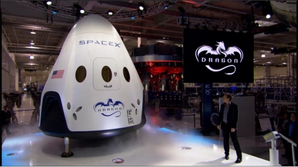 Elon Musk unveils a mock-up of the Dragon V2 capsule in May 2014. SpaceX now has their firs NASA contract to fly a crew to the ISS aboard the vehicle, probably in 2018