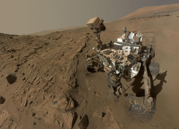 """Curiosity's selfie: all of the rover except the robot arm is visible in this composite image made up of shots taken before and after the """"Windjana"""" sample drilling - the hole from which is visible, lower left"""