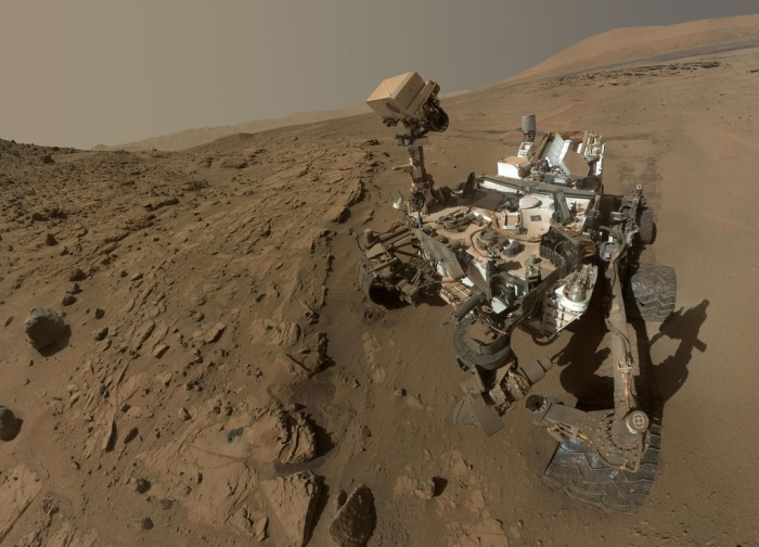"Curiosity's selfie: all of the rover except the robot arm is visible in this composite image made up of shots taken before and after the ""Windjana"" sample drilling - the hole from which is visible, lower left"