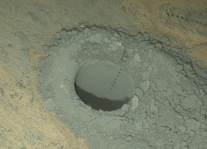 "A composite of eight shots from MAHLI showing successive strikes from the ShemCam laser, both within the sample drilling hole at ""Windjana"" and where the tailings have mixed with surface dust (top right). Such strikes allow the chemical coposition of the dust and rock to be analysed (click to enlrage)"