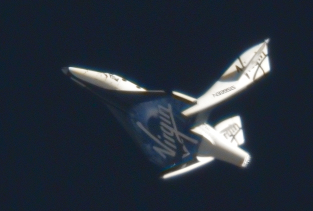 """SpaceShipTwo in full """"feathered"""" mode during an unpowered drop test in May, 2011 as a part of testing the feathering system, which saw the booms deployed to their full """"feather"""" position of 65 degrees for 1 minute Image via  Clay Centre Observatory/Virgin Galactic"""