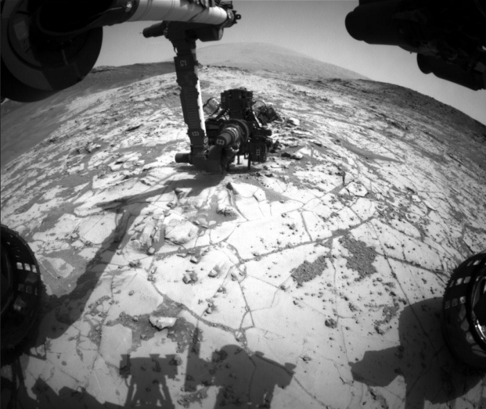 "A unique view of the ""mini drilling"" operation on ""Mojave"". Captured by Curiosity's Hazcam navigation cameras, the image shows the rover's ""hand"" oriented such that the dril (visible with its two steadying arms) is placed against the rock"
