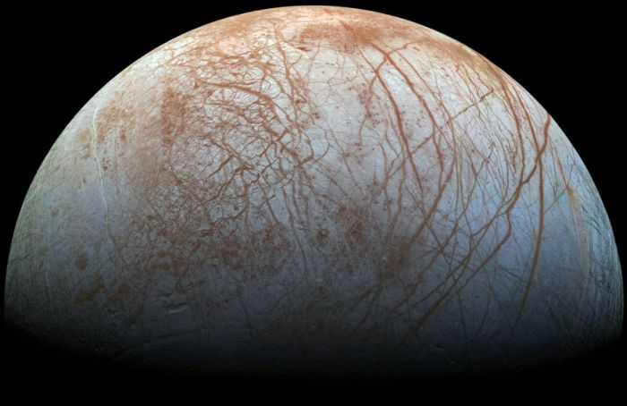 The surface of Europa: a crust of water ice sitting beneath a tenuous, oxygen-rich atmosphere and above a liquid water ocean, criss-crossed with stress lines and fractures