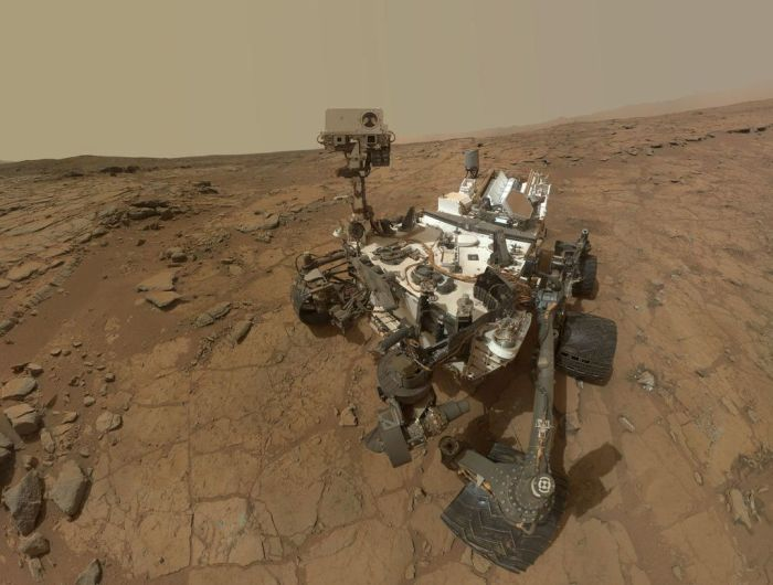 "An updated version of Curiosty's ""selfie"" from February 2013, when the rover was examining the rock dubbed ""John Klein"".  The original image rendered a ""fishbowl"" look; in this revised image, the background has been flatened and rendered as seen from a single point in the camera's field of view, while the view of Curiosity is made up of a number of images captured by the rover's Mars Hand Lens Imager (MAHLI)"