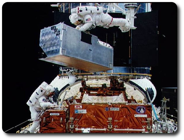 December 8th, 1993, astronaut Kathryn C. Thornton (top of this image)  holds on to the COSTAR package as the shuttle Endeavour's robot arm slowly lifts her - and -it - clear of its cradle in the shuttle's payload bay, ready for installation into Hubble