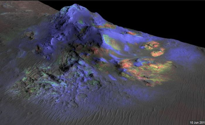A spectrographic image of the central peak of the Alga Crater impact zone, taken by MRO. The green colours indicate the presence of impact glass