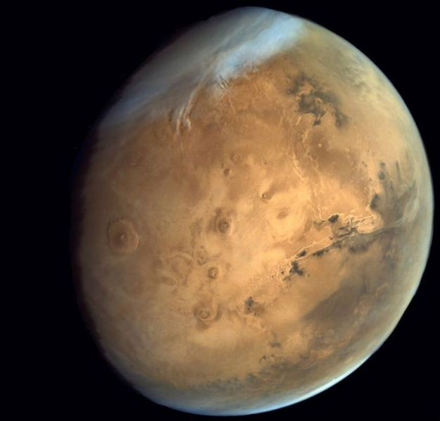 "Mars: The north polar ice cap, the three massive craters of the Tharsis volcanoes forming a diagonal line in the centre, the mighty ""boil"" of Olympus mons to their left and the 5,000 km long Vallis Marineris to their right"