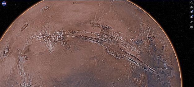 This 3D rendering from Mars Trek uses genuine data from NASA's 50 years in exploring Mars to present a surface model of the Red Planet, and I've positioned it to show it massive scale of the 5,000 km long Vallis Marineris, the great rip in the surface of Mars. To the upper left, the huge Tharsis volcanoes, among the biggest in the solar system, can be seen