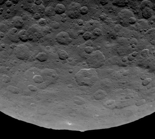 """The 5 km high """"pyramid"""" mountain pokes up above the limb of Ceres. Flat-topped, it has streaks of bight mateiral on its flanks giving the impression something has been flowing down it."""
