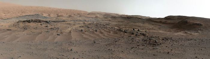 "A stunning vista: the slopes of ""Mount Sharp"" as seen by Curiosity as it commenced the upward drive away from ""Marias Pass"". Captured by the rover's Mastcam systems, the image shows an intriguing landscape, with the gravel and sand ripples typical of much of the terrain over which the rover has passed in the foreground. In the middle distance sit outcrops of smooth, dust-covered bedrock, above which sit sandstone ridges. On the horizon sit rounded buttes, rich in sulfate minerals, suggesting a change in the availability of water when they formed - click image for the full size version"