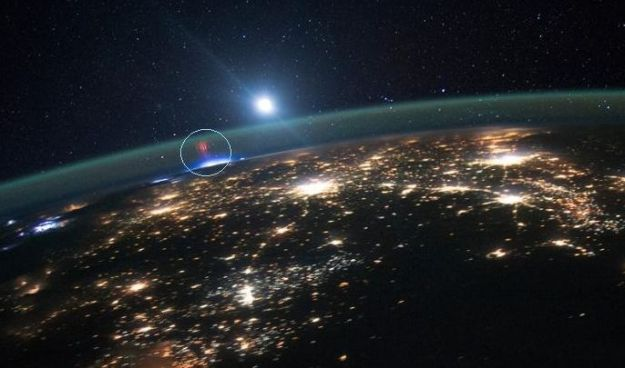 """Red lightning"" sprites imaged from the ISS: captured on August 10th, this picture shows elusive ""red lightning"" sprites occurring high in Earth's atmosphere above a thunderstorm (the bright area directly under them) in the mid-west USA. The surrounding yellowish lights are from towns and cities - image: NASA / JSC"