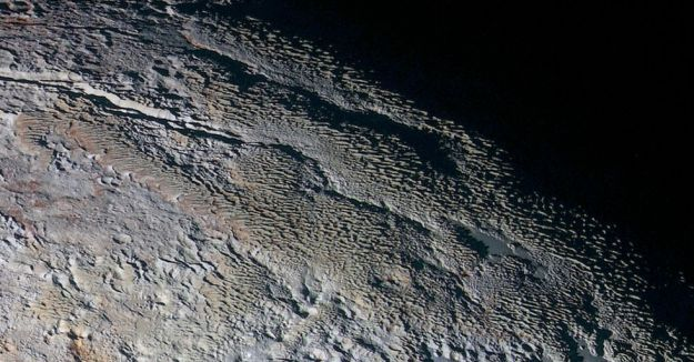 An extended colour image of the Tartarus Dorsa region of Pluto, showing rounded and bizarrely textured mountains which appear covered by intricate but puzzling patterns of blue-gray ridges with reddish material in between. This image is approximately This view, roughly 500 km (312 mi) resolves details and colors on scales as small as 1.3 km (0.8 mi) across (image: NASA/JHUAPL/SWRI)