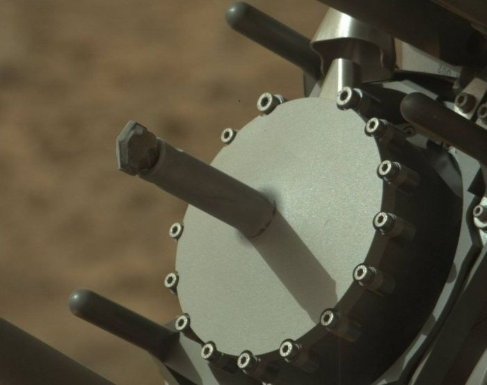 "A unique view of Curiosity's drilling following the sample gathering at ""Big Sky"". Captured by the rover's Mastcam, the image shows the drill head, couple with dusty drill bit. The tube surrounding it, coupled with the groves visible in the drill bit itself, is used to deliver tailings from the drilling into one of two sample ports in the circular drill head. Later, and by a process of vibration, these tailings are delivered to the CHIMRA ""sorting"" unit within the rover's robot ""hand"" which grades and sorts the sample material ready for onward transfer into Curiosity's analysis instruments"