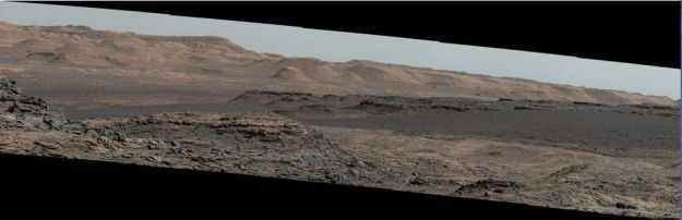 "A mosaic of images taken on September 25th, 2015 (Sol 1,115) captures by the right lens of the rover's Mastcam system. .The view is toward south-south-west and reveals the ""Bagnold Dunes"" as a dark band across the middle of the image, blending with mesas beyond them"