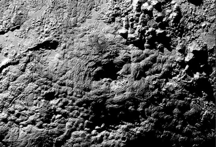 """Wright Mons"" in the centre of this image is a large mountainous feature south of ""Sputnik Planum"", topped by a crater-like depression at the top some 56 km (35 mi) across, is thought to be one of two large ""ice volcanoes"" see in the most recent images returned by New Horizons."