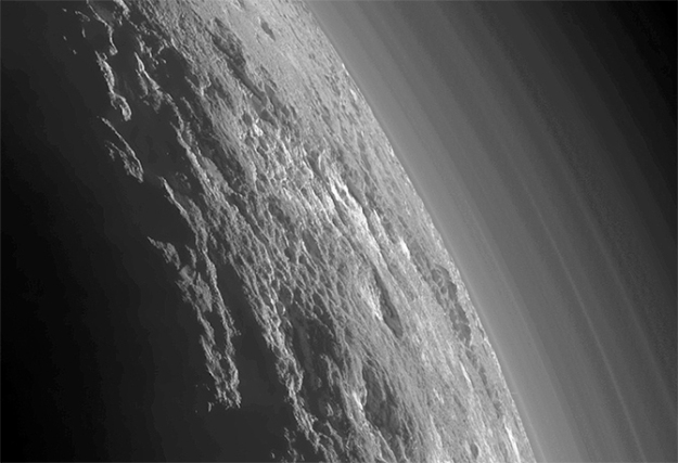 An enhanced image of Pluto north polar region revealing an incredibly complex surface of hills and valleys, ice features and high mountains, while above can be seen an enhanced view of the complex atmospheric banding