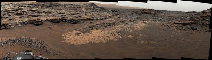 "This May 22, 2015, view from the Mast Camera (Mastcam) in NASA's Curiosity Mars rover shows the ""Marias Pass"" area where a lower and older geological unit of mudstone -- the pale zone in the center of the image -- lies in contact with an overlying geological unit of sandstone. This view from the Mast Camera (Mastcam) in NASA's Curiosity Mars rover shows the ""Marias Pass"" area where a lower and older geological unit of mudstone -- the pale zone in the center of the image -- lies in contact with an overlying geological unit of sandstone. Just before Curiosity reached Marias Pass, the rover's laser-firing Chemistry and Camera (ChemCam) instrument examined a rock found to be rich in silica, a mineral-forming chemical. This scene combines several images taken on May 22, 2015, during the 992nd Martian day, or sol, of Curiosity's work on Mars. The scene is presented with a color adjustment that approximates white balancing, to resemble how the rocks and sand would appear under daytime lighting conditions on Earth."