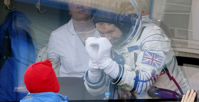 Peake, aboard the crew bus and about to depart for the launch pad, shows his love for one of his toy young boys (Image: The Guardian)
