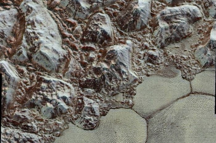 "A ture colour image of Pluto's surface, captures just before the point of closest approach, and created by combining black-and-while images from from the LORRI camera with data gathered by the Ralph instrument suite. The picture show the highlands to one side of ""Sputnik Planum with the pockmarked ices of the basin. A combination of evaporation and condensation between the two is giving rise to sustained glaciation on Pluto, showing it to be an active world"