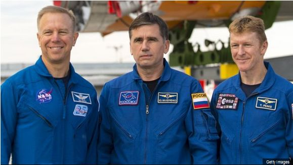 Yuri Malenchenko flanked by Tim kopra (l) and Tim Peaker (r), pictured on Saturday, December 12th, as their Soyuz craft atop its booster - just visible in the background - was rolled out to the launchpad at Baikonaur Cosmodrome