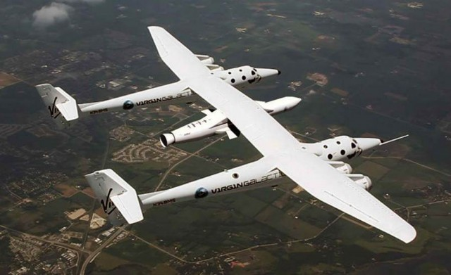White Knight Two flying to the Farnborough air Show in 2012 with a mock-up of the original LauncherOne mounted beneath it (Image: Virgin Galactic)