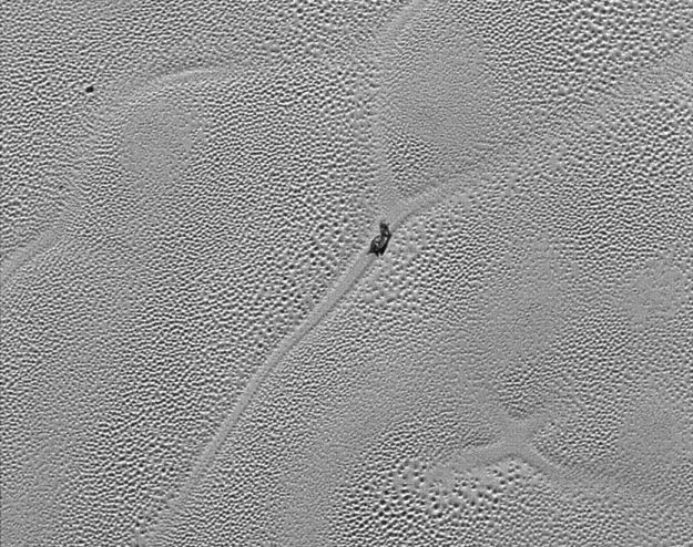 "A close-up of the ""Sputnik Planum"" ice field, showing the ""cells"" of ice between 16 and 38 km across, which are thought to be under motion from convection currents operating beneath them. The slug-like object in the centre of the image is believed to be a large dirty iceberg of water ice, ""floating"" on the denser nitrogen ice (image: NASA / JHU/APL / SwRI)"