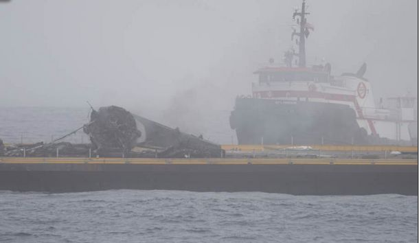 With the towing vessel for the autonomous droneship approaching in the background, a photo from one of the landing support vessels shows the Falcon 9 1st stage toppled over on the landing ship's deck after one of its legs broke on touchdown