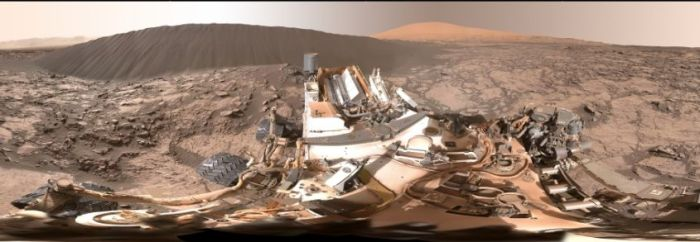 "This rather odd-looking image is a foreshortened 360-degree view of the area around Curiosity. In the immediate foregound is the rover's main deck, with the cylindrical, finned nuclear RTG at the back of it. Beyond this is the ""Namib"" dune, with a taller dune beyond it. The view was constructed froma series of images taken by the rover's Mastcam on December 18th, 2015 (Sol 1,197 on Mars), all of which have been white-balanced to present the view under normal Earth daylight conditions"
