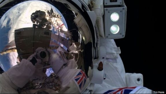 A selfie by Major Tim during his EVA, the camera visible in the reflection in his helmet visor