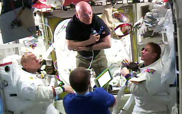 Current station commander Scott Kelly (top) is flanked by Kopra and Peake after their return to the station, to discuss Kopra's suit issue