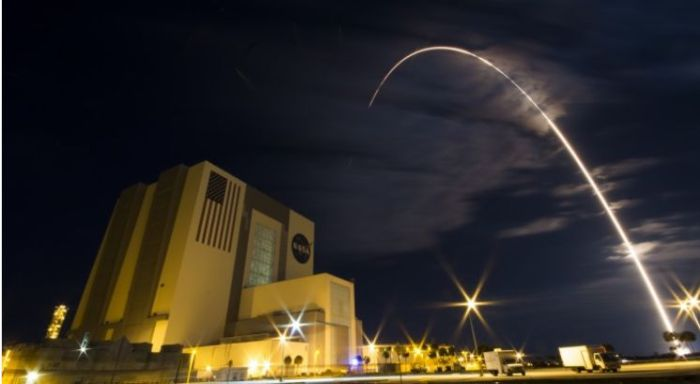 "Long exposure photograph shows the trail of the Atlas V launch vehicle as it carries the Cygnus OA6 vehicle ""Rick Husband"" into orbit on March 22nd, 2016. In the foreground is the world famous Vehicle Assembly Building (VAB) at NASA's Kennedy Space Centre (credit: Alex Polimeni / Spaceflight Now)"