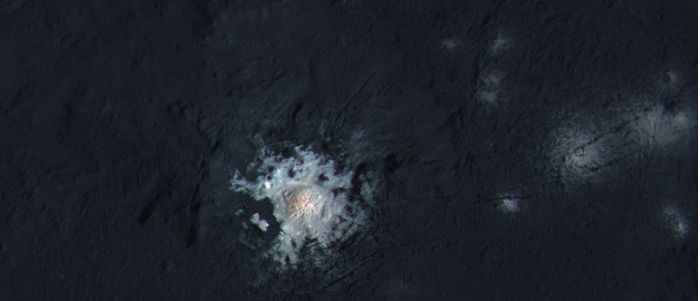 A false-colour image showing the main peak in Occator crater with the small bright spots off to the right