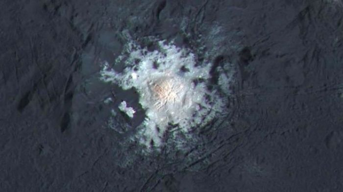 "A true colour image returned by the Dawn space probe of one of the bright ""spots"" in Occator crater on Ceres, revealing what might be a cryo-volcano"