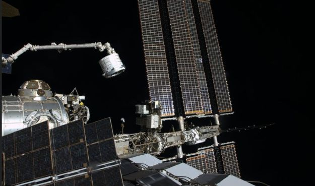 Space station commander Tim Kopra took this photograph of the BEAM unit, in its compact state, being moved towards the Tranquillity module by the station's robot arm, ready for it to be secured against one of the station's airlocks