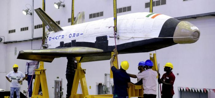 The RLV-TD about to by hoisted for mating to its launch booster. Credit: ISRO