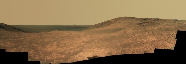 A composite mosaic of images captured by Opportunity's panoramic imaging system in April / May 2016, showing the fractured nature of Marathon Valley in the foreground and the darker mass of Endeavour crater beyond. Credit: NASA/JPL / Cornell Univ. / Arizona State Univ.