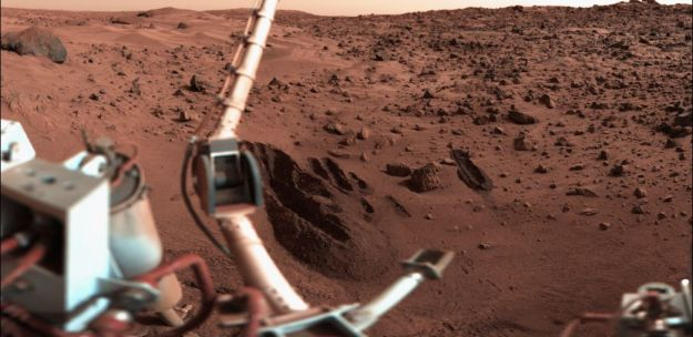 "The Viking 1 Lander sampling arm created a number of deep trenches as part of the surface composition and biology experiments on Mars. In this image, the digging tool on the sampling arm can be seen lower centre, The boom holding the meteorology sensors is on the left, as the camera system looks out over the ""sandy flats"" of Chryse Planitia. Credit: Nasa / public domain"