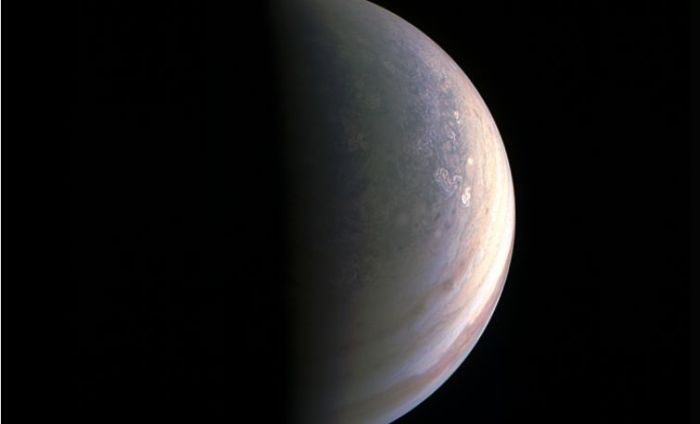 Captured at a distance of 78,000 km (48,000 mi) from Jupiter by JunoCam, this image reveals the pale bluish region of Jupiter's north polar region, speckled by hurricane-like cloud formations