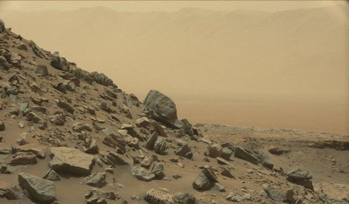 """A dramatic look back: in the foreground is the lower slope of one of the """"Murray Buttes"""", in the far distance the tall peaks of Gale Crater's huge rim. One of the final images taken by Curiosity from within the region of the buttes on Thursday, September 8th, the rover's 1,454 sol on Mars. Credit: NASA/JPL / MSSS"""