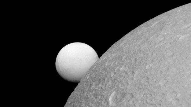 "NOT an artist's impression. This is an actual image of Dione (foreground) with Enceladus ""sitting"" on its limb, captured by the Cassni spacecraft on September 8th, 2015. NASA/JPL-Caltech/SpS Institute"