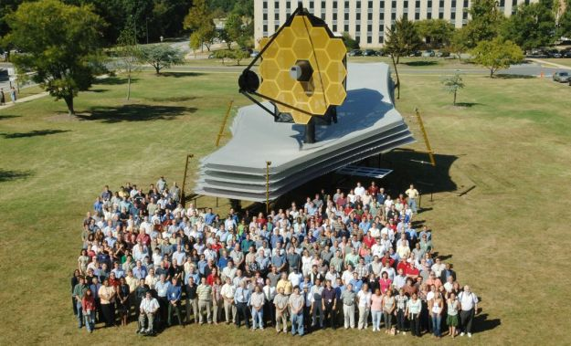 """A full scale model of the JWST at NASA's Goodard Spaceflight Centre, Maryland, showing the segmented primary mirror (top), the layered """"cells"""" of the sunshield, designed to protect the science instruments and mirror from the heat and light of the sun (in grey), with the solar power arrays just visible underneath. Standing before the model is the JWST team from Goddard Credit: NASA Goddard Spaceflight Centre"""