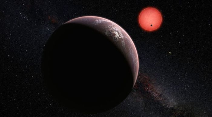 "The three planets of the TRAPPIST-1 system seen an an artist's impression. One of the planets is seen orbiting its parent star, an ultra cool dwarf star, and the second can be seen as a small arc at the 5-o'clock position, Known as TRAPPIST-1b and TRAPPIST-1c, they occupy the so-called ""Goldilocks zone"" around the star. The third planet in they system (foreground), called TRAPPIST-1d sits outside the critical zone, but may also have an atmosphere"
