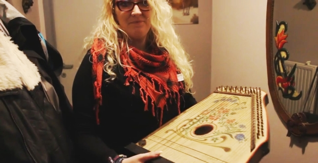 Jaimy Hancroft and two of her father's creation: a warnamandal, and on the wall behind her, a mirror painted by Mario