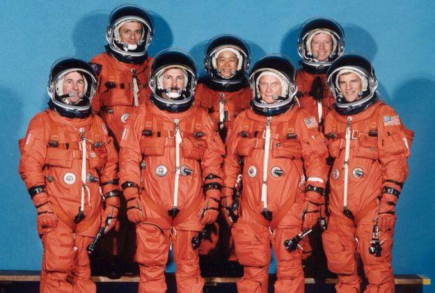 The STS-95 Discovery crew in a pose reminiscent of some of the Mercury 7 publicity shots. (l-r): Stephen K. Robinson; Pedro Duque (ESA); Curtis L. Brown Jr. (Mission Commander); Chiaki Mukai (NASDA); Senator John Glenn; Steven W. Lindsey (Shuttle Pilot) and Scott F. Parazynski. Credit: NASA