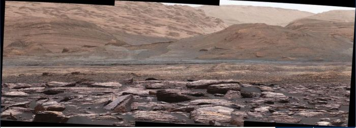 "A mosaic of Mastcam images captured by NASA's Curiosity rover on November 10th, 2016 (Sol 1,516), showing the lower slopes of ""Mount Sharp"". Variations in the rocks colour hint at the diversity of their composition. The purple tone of the foreground rocks has been seen in other rocks where hematite has been detected. Winds and windblown sand help to keep rocks relatively free of dust which would otherwise obscure their colour differentiation. These images have been white balanced, so the scene appears as it would under typical Earth daylight conditions"