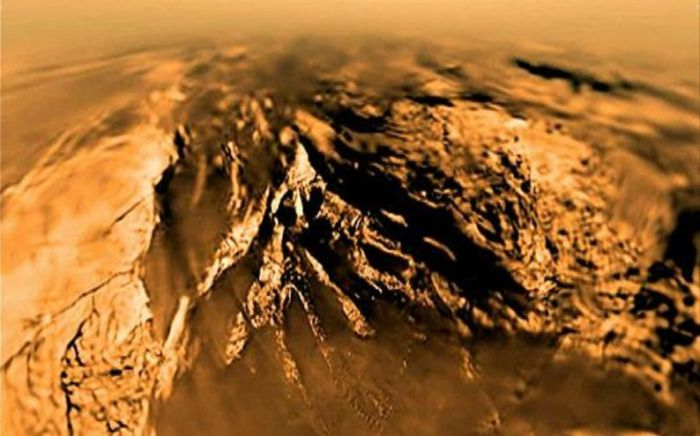 Titan as seen by Huygens from an altitude of 7 km (4.4 mi) on January 14th, 2005, with the probe still some 20 minutes from touchdown. The curvature evident in the image is an artefact of the image system and distortion due to the atmosphere. Credit: ESA
