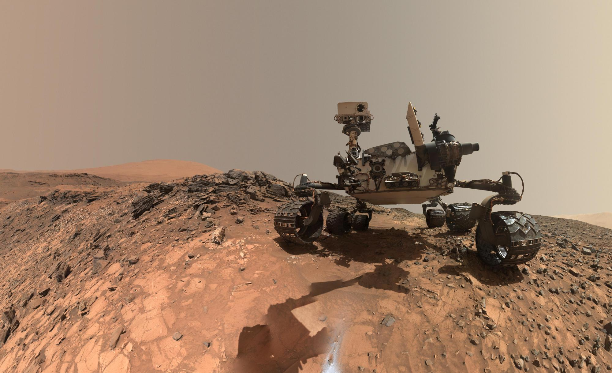 "Curiosity took this selfie while at ""Yellowknife Bay"" in 2013 whilst gathering rock samples for analysis. Note that while the shadow of the rover's robot arm can be assn, the arm itself is blanked from the images purely as a result of the angles used in individual shots and the way the images have been stitched together to provide a view of the rover"