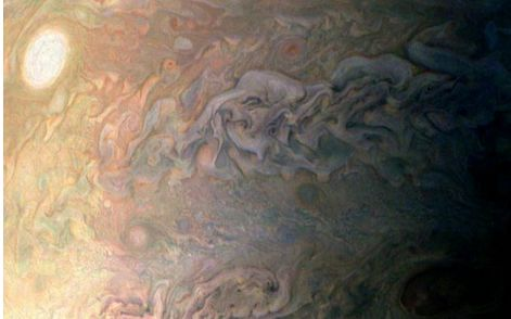 A stunning view of the intricate boundaries between Jupiter's bands of cloud, as captured by JunoCam during the December close pass over the cloud tops in December. The white spot is one of the