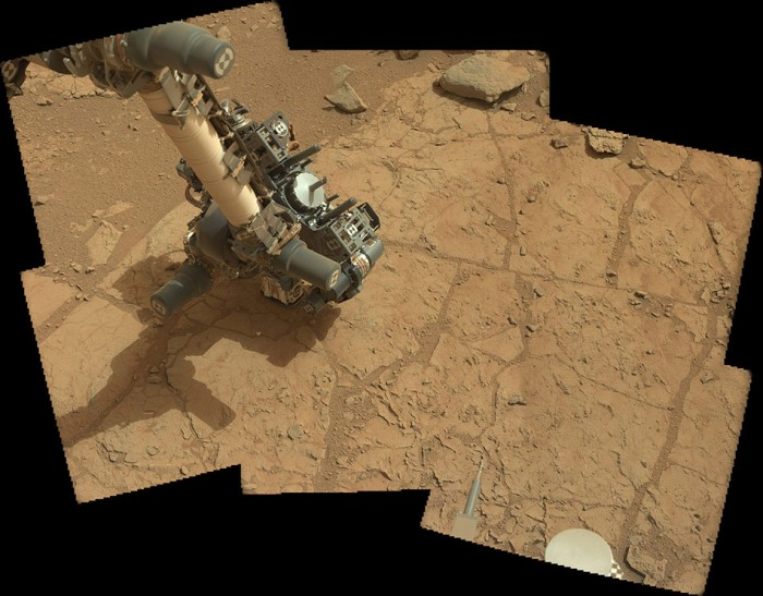 "Curiosity uses a spectrometer on its robot arm to check a rock dubbed ""John Klein"" in ""Yellowknife Bay"" for its suitability as a drilling target, January 25th, 2013. The drill itself can be seen on the robot arm's ""hand"", pointing up and to the right"